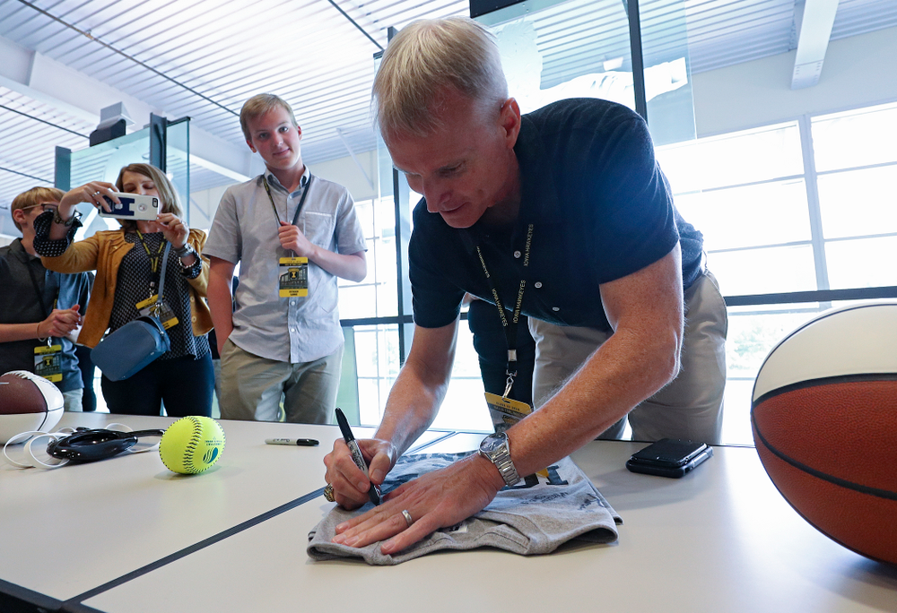 2019 University of Iowa Athletics Hall of Fame inductee and head swimming and diving coach Marc Long signs a shirt at the University of Iowa Athletics Hall of Fame in Iowa City on Friday, Aug 30, 2019. (Stephen Mally/hawkeyesports.com)