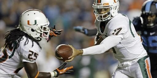 Miami quarterback Stephen Morris (17) hands off to Dallas Crawford (25) during the first half of an NCAA college football game against North Carolina...