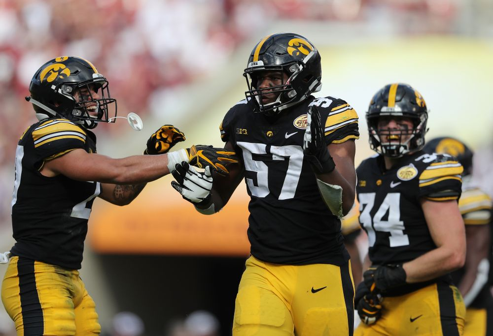Iowa Hawkeyes defensive end Chauncey Golston (57) celebrates with defensive back Amani Hooker (27) after intercepting a pass during the Outback Bowl Tuesday, January 1, 2019 at Raymond James Stadium in Tampa, FL. (Brian Ray/hawkeyesports.com)