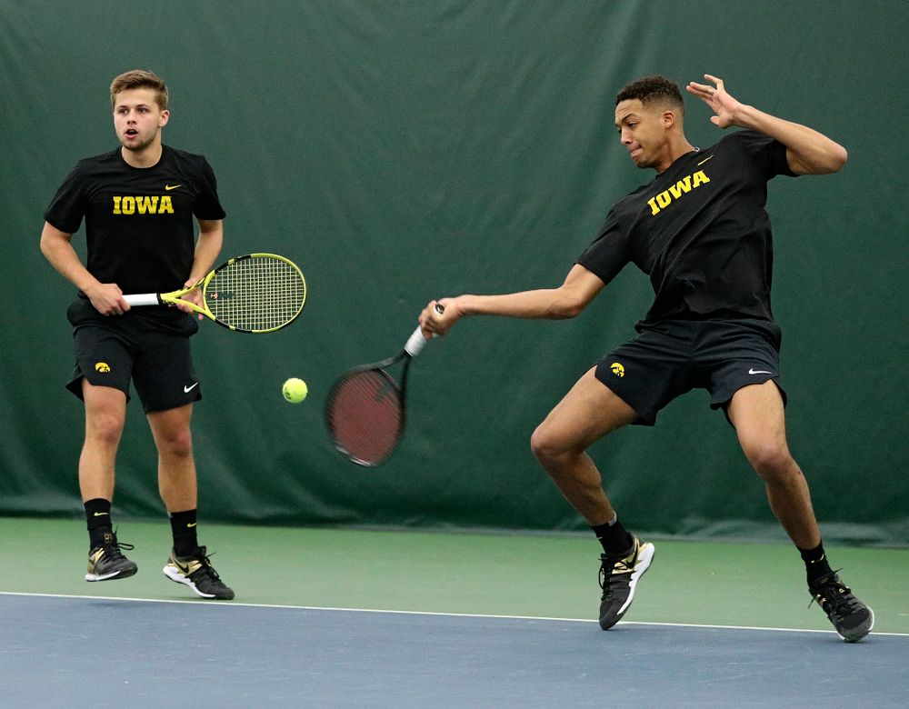 Iowa's Oliver Okonkwo (right) returns a shot as Will Davies (left) looks on during their doubles match at the Hawkeye Tennis and Recreation Complex in Iowa City on Friday, February 14, 2020. (Stephen Mally/hawkeyesports.com)