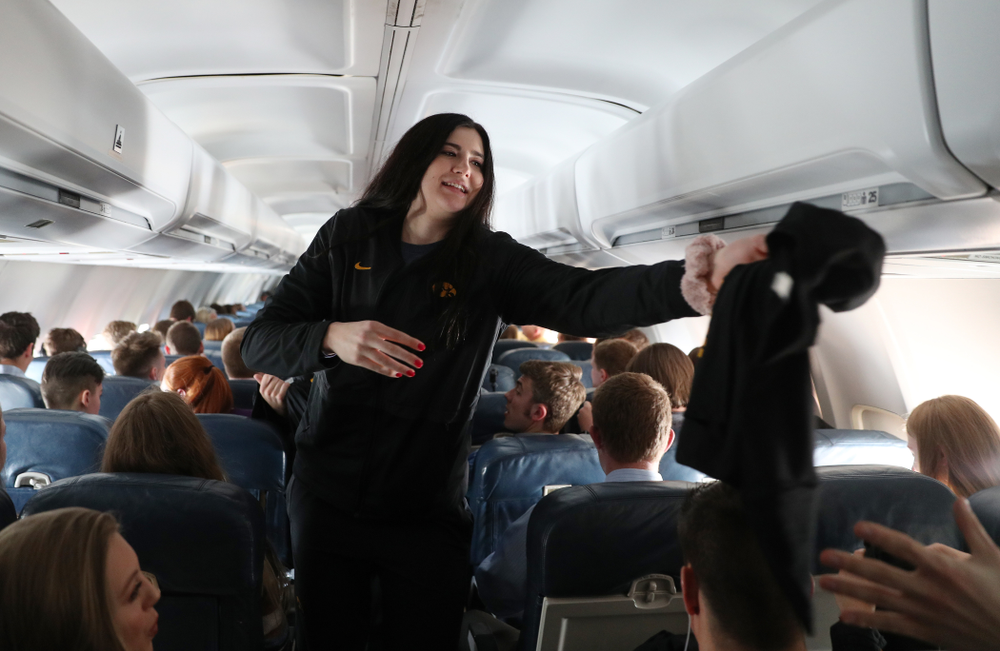 Iowa Hawkeyes forward Megan Gustafson (10) hands out t-shirts to the band and spirit squad on board the team plane to Greensboro, NC for the Regionals of the 2019 NCAA Women's Basketball Championships Thursday, March 28, 2019 at the Eastern Iowa Airport. (Brian Ray/hawkeyesports.com)