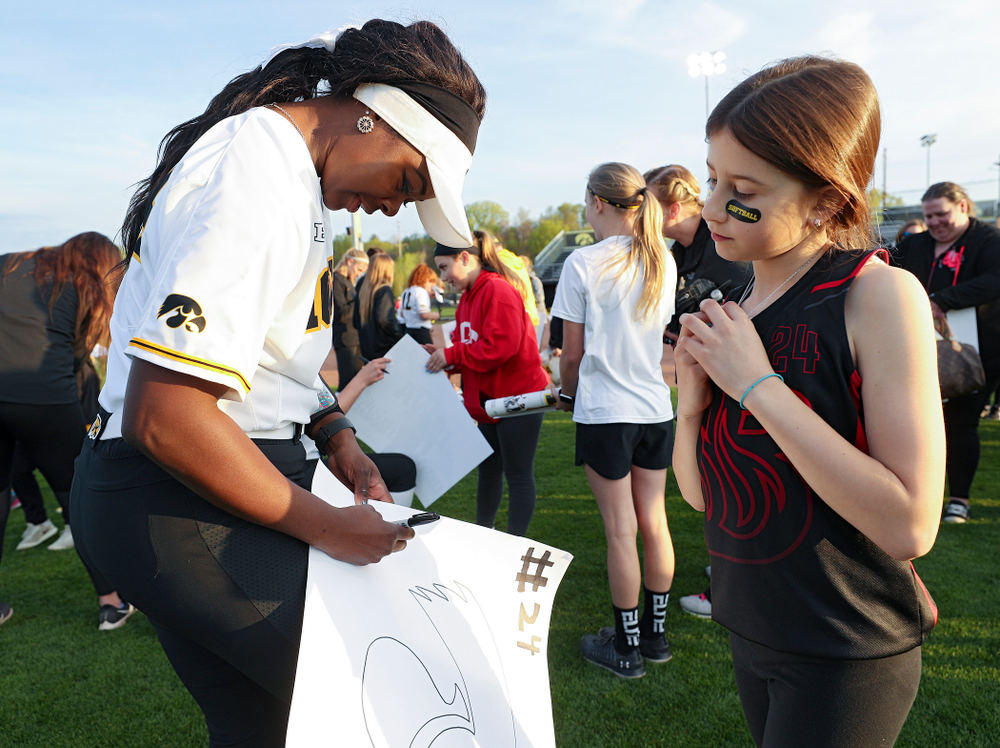 Iowa's DoniRae Mayhew (24) signs a poster for a fan after winning their game against Ohio State at Pearl Field in Iowa City on Friday, May. 3, 2019. (Stephen Mally/hawkeyesports.com)