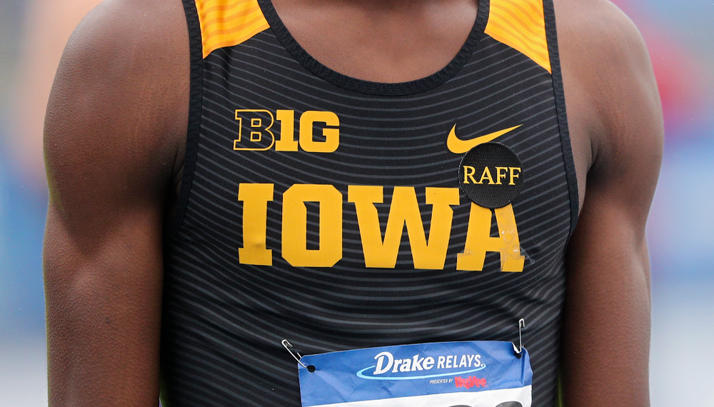 """Iowa's Wayne Lawrence Jr. wears a """"Raff"""" sticker in memory of the late Iowa volunteer assistant coach John Raffensperger before the men's 1600 meter relay event during the third day of the Drake Relays at Drake Stadium in Des Moines on Saturday, Apr. 27, 2019. (Stephen Mally/hawkeyesports.com)"""