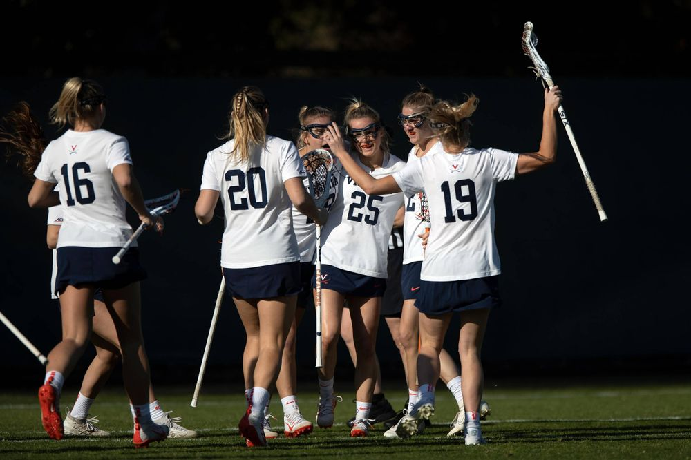 STANFORD, California - FEBRUARY 14:  Virginia Cavaliers midfield Courtlynne Caskin (25) is congratulated by teammates after scoring a goal against the Stanford Cardinal during the first half at Cagan Stadium on February 14, 2020 in Stanford, California. The Virginia Cavaliers defeated the Stanford Cardinal 12-11. (Photo by Jason O. Watson)