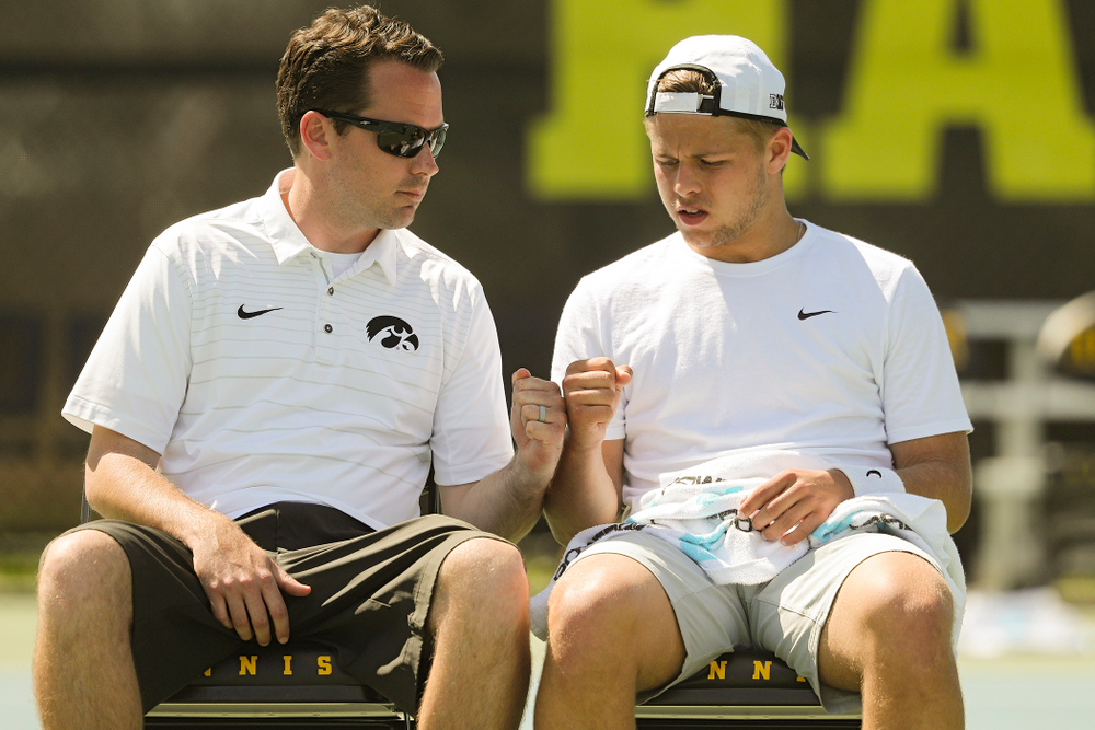 Iowa head coach Ross Wilson (from left) fist bumps Will Davies during his match against Michigan at the Hawkeye Tennis and Recreation Complex in Iowa City on Sunday, Apr. 21, 2019. (Stephen Mally/hawkeyesports.com)