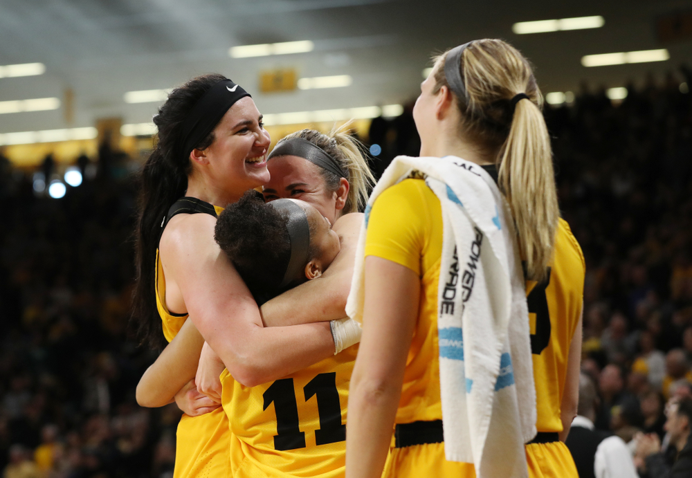 Iowa Hawkeyes forward Megan Gustafson (10) hugs guard Tania Davis (11) and forward Hannah Stewart (21) after they were taken out of the game against the Northwestern Wildcats Sunday, March 3, 2019 at Carver-Hawkeye Arena. (Brian Ray/hawkeyesports.com)