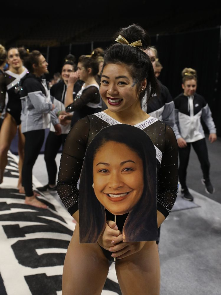 Iowa's Clair Kaji holds a photo of head coach Larissa Libby during their meet against the Rutgers Scarlet Knights Saturday, January 26, 2019 at Carver-Hawkeye Arena. (Brian Ray/hawkeyesports.com)
