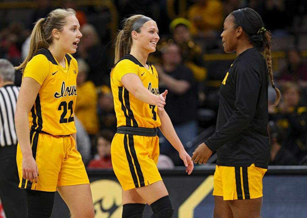 Iowa Hawkeyes guard Makenzie Meyer (3) gets a high-five from guard Zion Sanders (21) as she heads to the bench for a timeout with guard Kathleen Doyle (22) during the fourth quarter of their game at Carver-Hawkeye Arena in Iowa City on Thursday, January 23, 2020. (Stephen Mally/hawkeyesports.com)