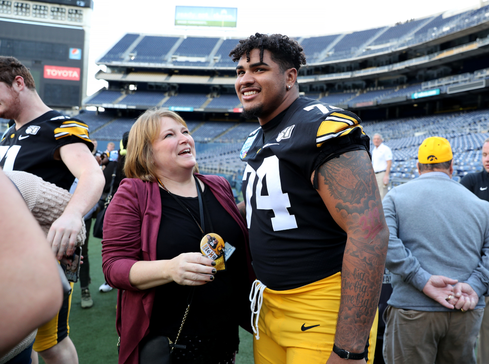 Iowa Hawkeyes offensive lineman Tristan Wirfs (74) hugs family members of Kyler Schott following the team photo Wednesday, December 25, 2019 at SDCCU Stadium in San Diego. (Brian Ray/hawkeyesports.com)