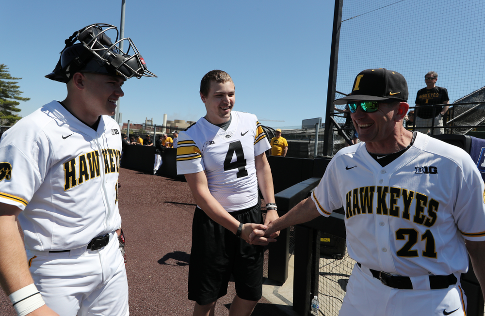 Iowa Hawkeyes quarterback Nate Stanley (4) shakes hands with Iowa Hawkeyes head coach Rick Heller before throwing out a first pitch against the Nebraska Cornhuskers Saturday, April 20, 2019 at Duane Banks Field. (Brian Ray/hawkeyesports.com)