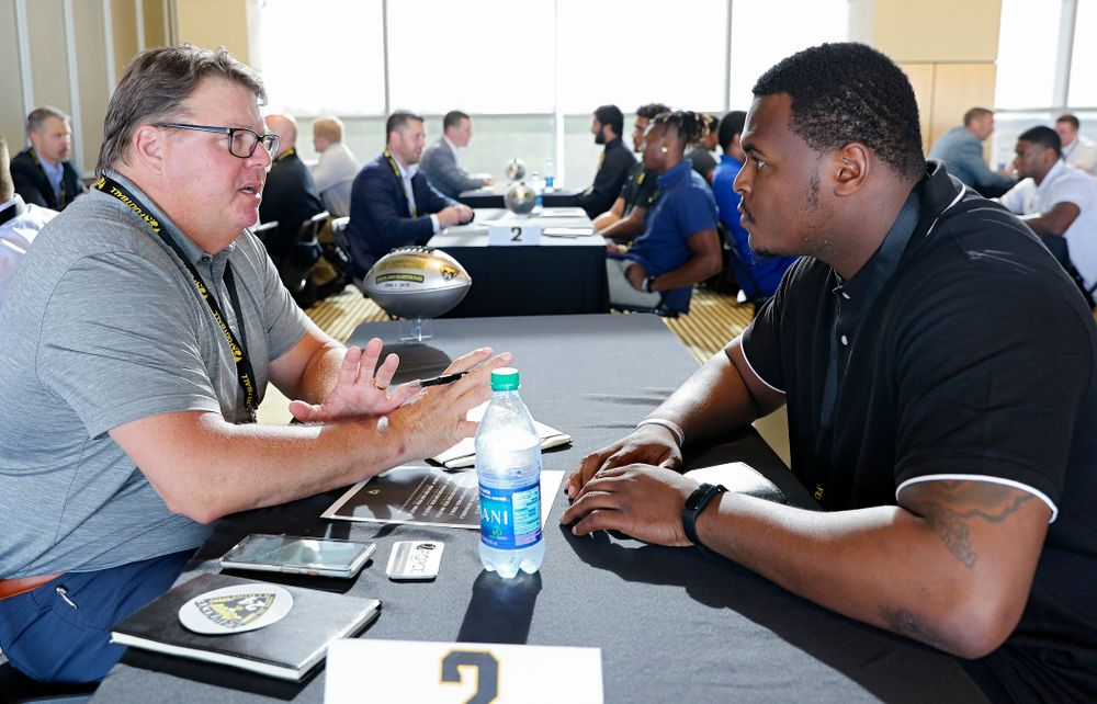 Hap Peterson (from left), former Iowa defensive lineman, talks with defensive lineman Cedrick Lattimore as former players meet with members of the current Hawkeye Football team during a networking event at Kinnick Stadium in Iowa City on Thursday, Jun 6, 2019. (Stephen Mally/hawkeyesports.com)