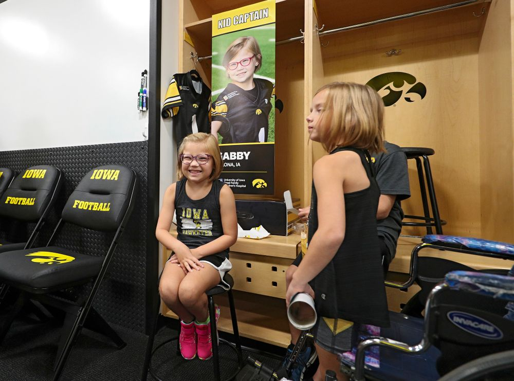 Kid Captain Gabby Yoder sits at her locker during Kids Day at Kinnick Stadium in Iowa City on Saturday, Aug 10, 2019. (Stephen Mally/hawkeyesports.com)
