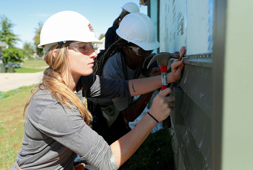 Iowa's Kate Martin hammers in a nail on a piece of siding as they work on a Habitat for Humanity Women Build project in Iowa City on Wednesday, Sep 25, 2019. (Stephen Mally/hawkeyesports.com)