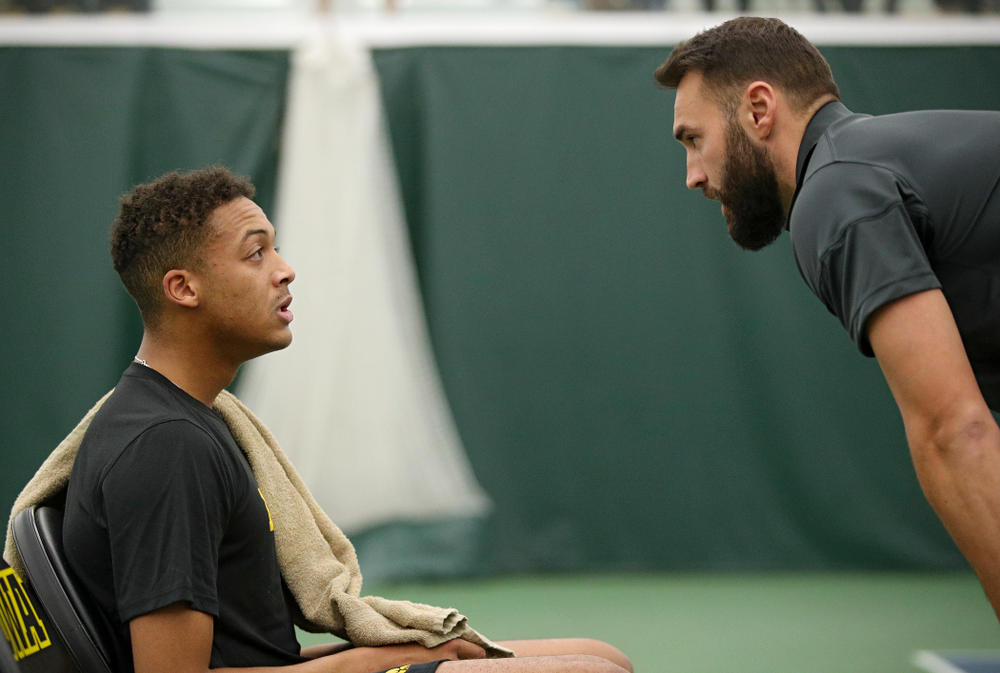 Iowa's Oliver Okonkwo (from left) talks with assistant coach Lloyd Bruce-Burgess during his match against Marquette at the Hawkeye Tennis and Recreation Complex in Iowa City on Saturday, January 25, 2020. (Stephen Mally/hawkeyesports.com)