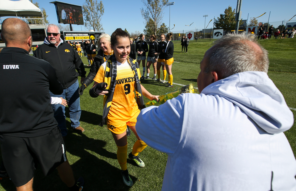 Iowa Hawkeyes head coach Dave DiIanni presents Iowa Hawkeyes defender Karsen Rauch (9) with a framed photo during Senior Day ceremonies before a game against Northwestern at the Iowa Soccer Complex on October 21, 2018. (Tork Mason/hawkeyesports.com)