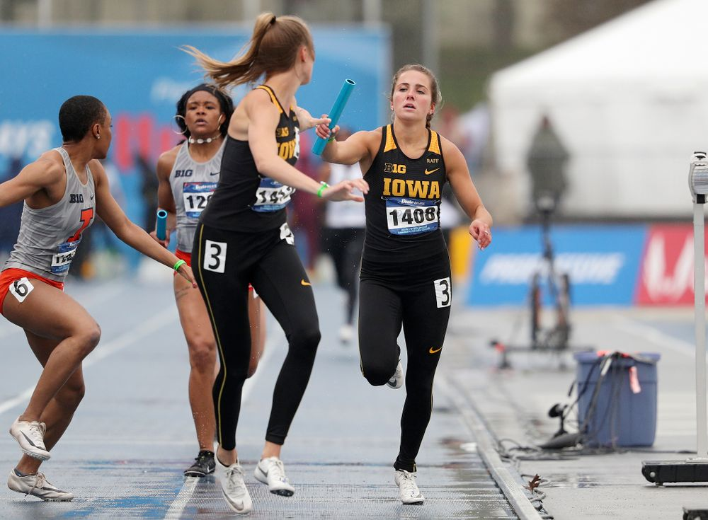 Iowa's Addie Swanson (right) hands the baton off to Payton Wensel as they run the women's 1600 meter relay event during the third day of the Drake Relays at Drake Stadium in Des Moines on Saturday, Apr. 27, 2019. (Stephen Mally/hawkeyesports.com)