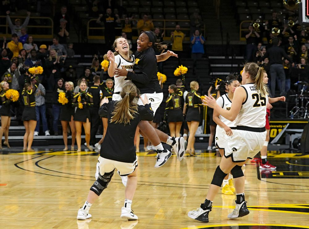 Iowa Hawkeyes guard Kathleen Doyle (22), guard Zion Sanders (21), and guard Kate Martin (20) celebrate after their double overtime win at Carver-Hawkeye Arena in Iowa City on Sunday, January 12, 2020. (Stephen Mally/hawkeyesports.com)