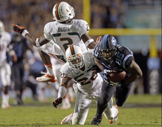 North Carolina's Eric Ebron (85) gains some yardage following a pass reception as Miami's Deon Bush (2) and  Rayshawn Jenkins defend during the first...