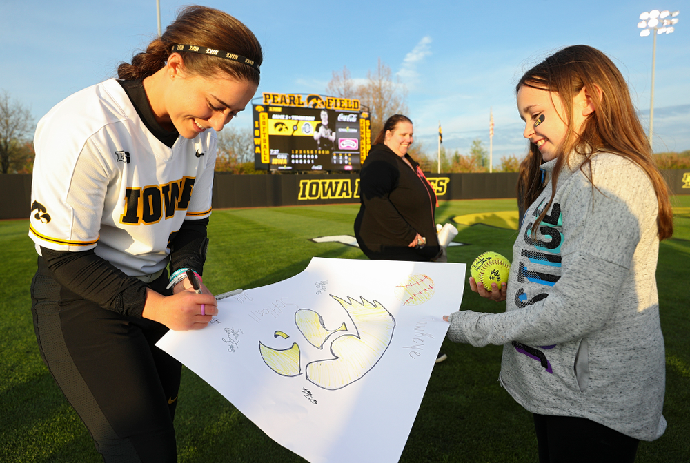 Iowa's Elizabeth DeShields (19) signs a poster for a fan after winning their game against Ohio State at Pearl Field in Iowa City on Friday, May. 3, 2019. (Stephen Mally/hawkeyesports.com)