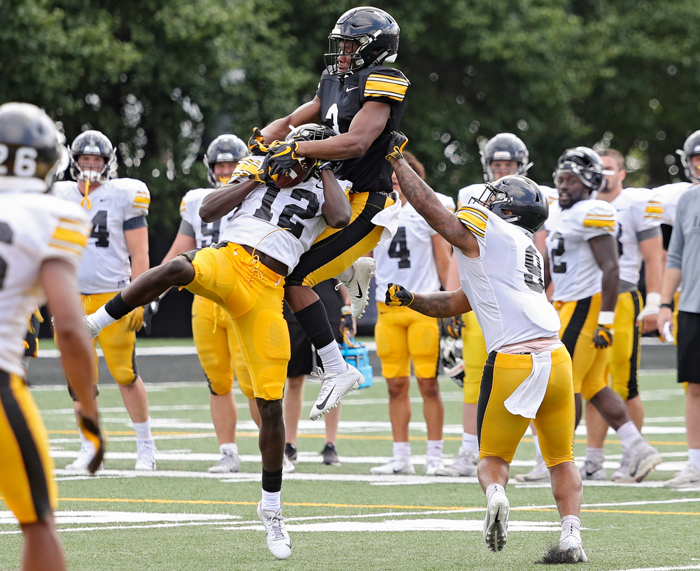 Iowa Hawkeyes defensive back D.J. Johnson (12) intercepts a pass intended for wide receiver Tyrone Tracy Jr. (3) as defensive back Geno Stone (9) closes in during Fall Camp Practice No. 11 at the Hansen Football Performance Center in Iowa City on Wednesday, Aug 14, 2019. (Stephen Mally/hawkeyesports.com)
