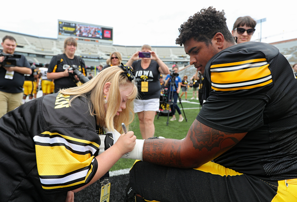 Kid Captain Kendra Hines signs the tape on the arm of Iowa Hawkeyes offensive lineman Tristan Wirfs (74) during Kids Day at Kinnick Stadium in Iowa City on Saturday, Aug 10, 2019. (Stephen Mally/hawkeyesports.com)