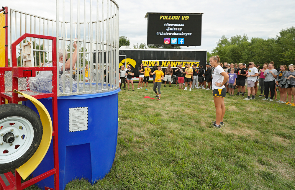Iowa Softball's Aralee Bogar sinks Swimming head coach Marc Long in the dunk tank during the Student-Athlete Kickoff outside the Karro Athletics Hall of Fame Building in Iowa City on Sunday, Aug 25, 2019. (Stephen Mally/hawkeyesports.com)