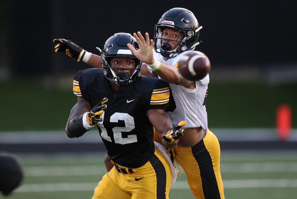 Iowa Hawkeyes wide receiver Brandon Smith (12) & defensive back Julius Brents (20)