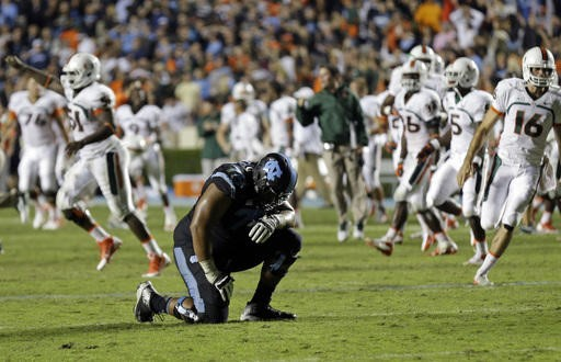 North Carolina's Landon Turner (78) kneels following North Carolina's loss to Miami in an NCAA college football game in Chapel Hill, N.C., Thursday,...