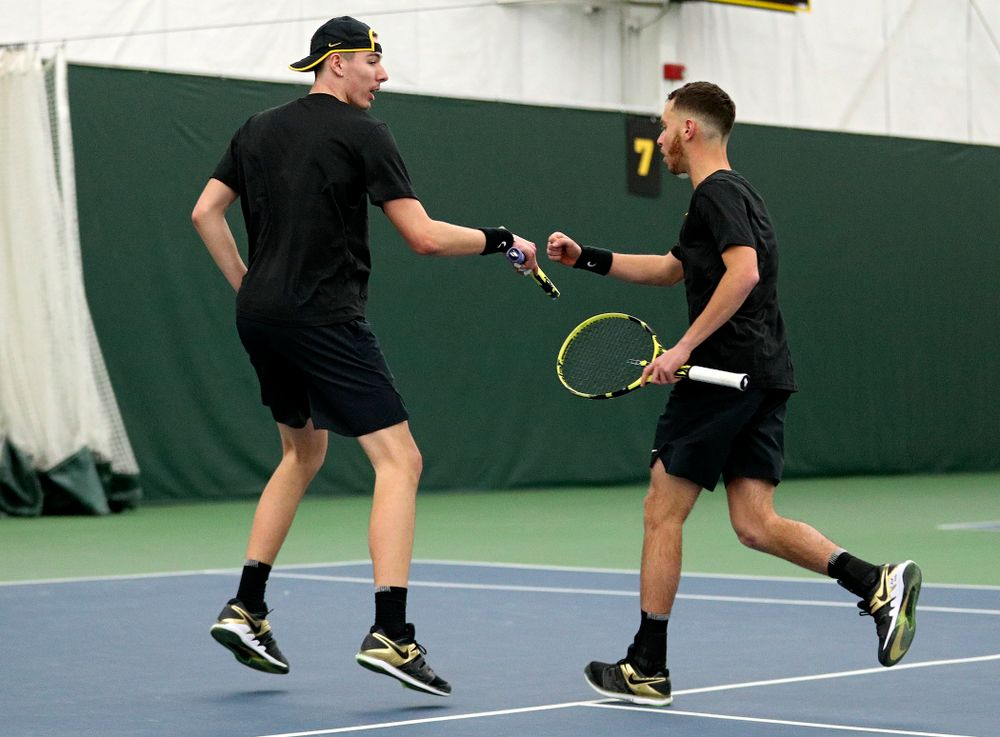 Iowa's Nikita Snezhko (from left) and Kareem Allaf fist bump as they celebrate during their doubles match at the Hawkeye Tennis and Recreation Complex in Iowa City on Friday, February 14, 2020. (Stephen Mally/hawkeyesports.com)