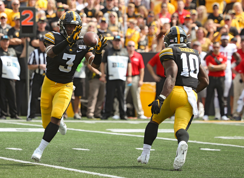 Iowa Hawkeyes running back Mekhi Sargent (10) tosses the ball to wide receiver Tyrone Tracy Jr. (3) during the third quarter of their Big Ten Conference football game at Kinnick Stadium in Iowa City on Saturday, Sep 7, 2019. (Stephen Mally/hawkeyesports.com)