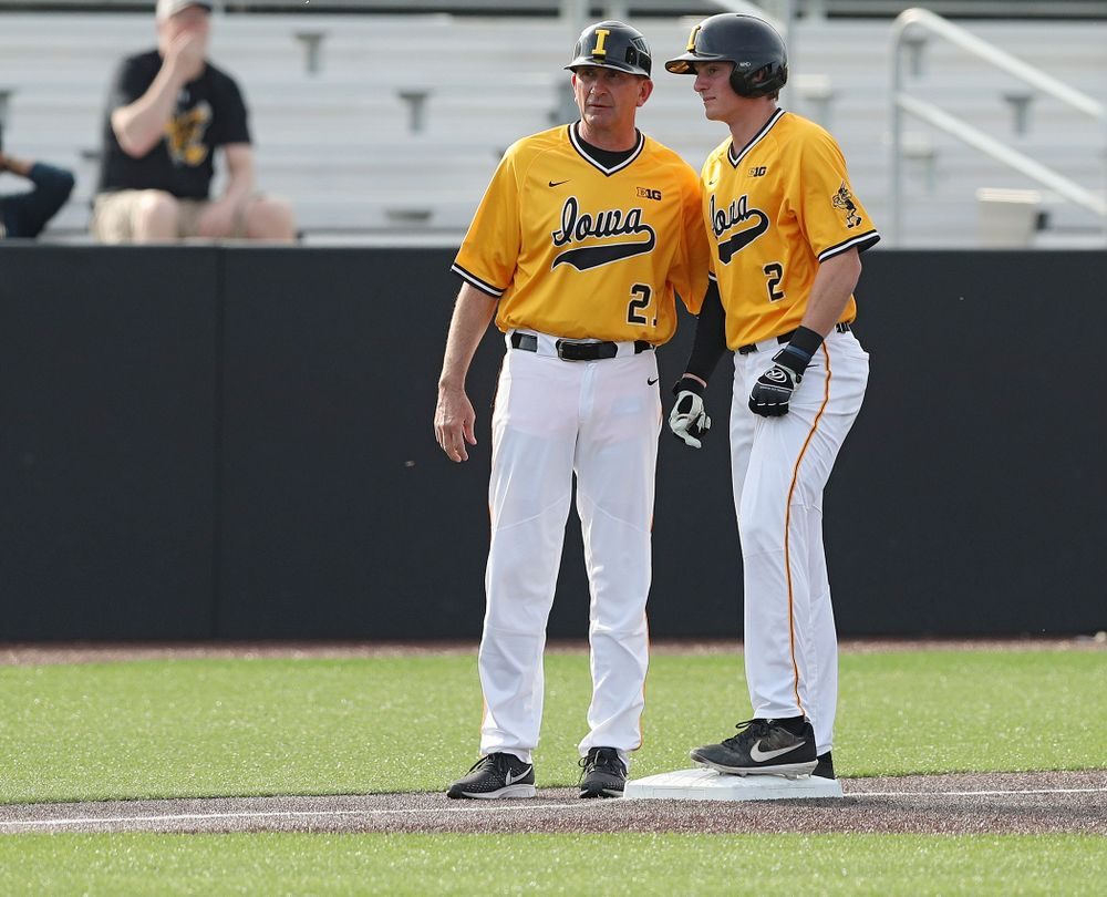 Iowa Hawkeyes head coach Rick Heller (from left) talks with second baseman Brendan Sher (2) on third base during the third inning of their game against Northern Illinois at Duane Banks Field in Iowa City on Tuesday, Apr. 16, 2019. (Stephen Mally/hawkeyesports.com)