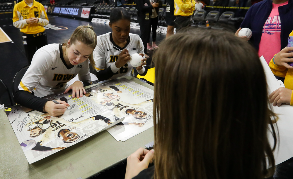Iowa Hawkeyes outside hitter Meghan Buzzerio (5) and Iowa Hawkeyes outside hitter Taylor Louis (16) sign autographs for fans after a match against Rutgers at Carver-Hawkeye Arena on November 2, 2018. (Tork Mason/hawkeyesports.com)