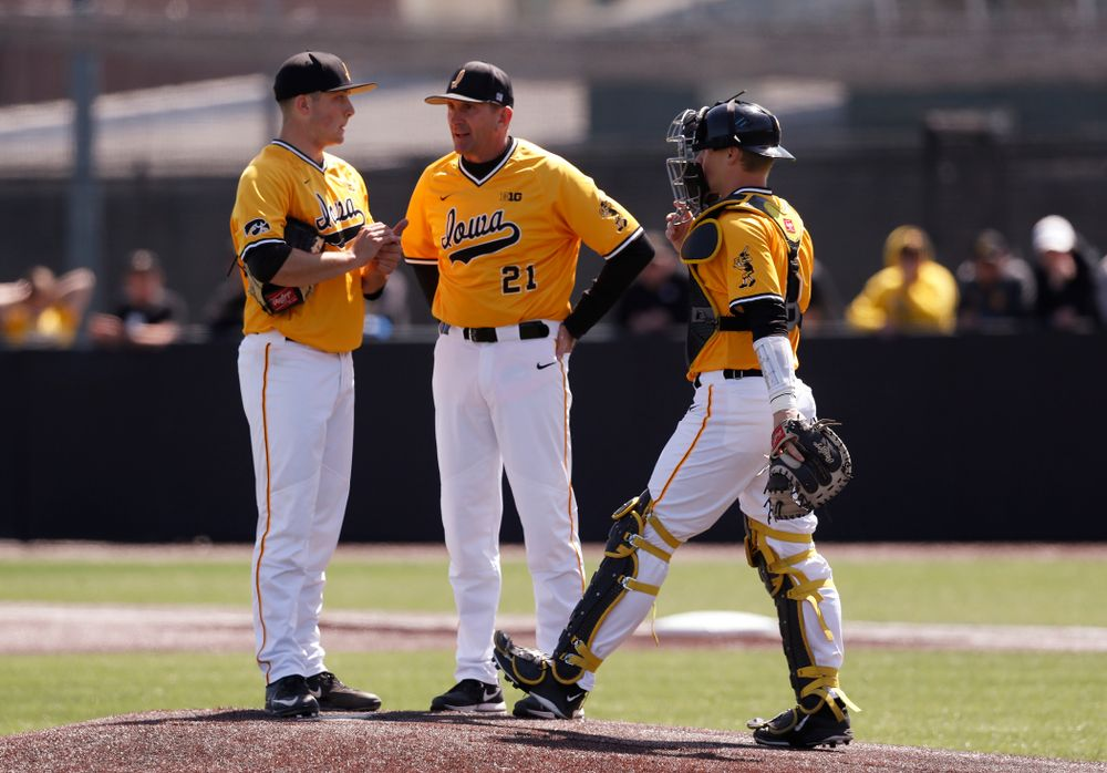 Iowa Hawkeyes pitcher Cole McDonald (11), catcher Tyler Cropley (5), and head coach Rick Heller against the Michigan Wolverines Sunday, April 29, 2018 at Duane Banks Field. (Brian Ray/hawkeyesports.com)