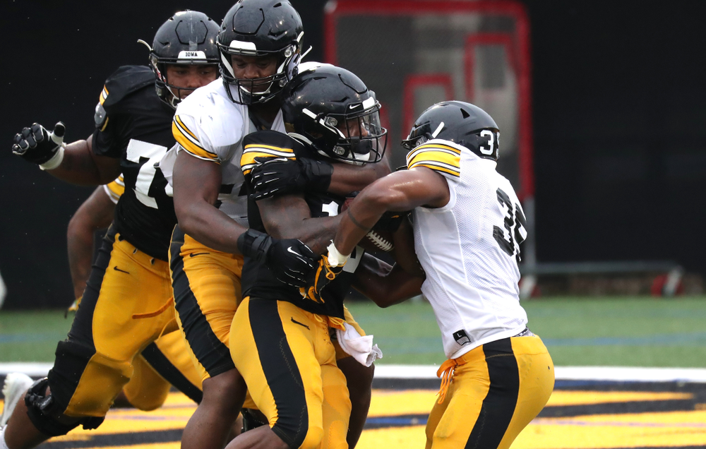 Iowa Hawkeyes defensive end Chauncey Golston (57) and Linebacker Barrington Wade (35) tackle running back Mekhi Sargent (10)