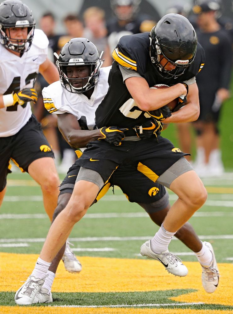 Iowa Hawkeyes wide receiver Jackson Ritter (29) is wrapped up by defensive back D.J. Johnson (12) during Fall Camp Practice No. 15 at the Hansen Football Performance Center in Iowa City on Monday, Aug 19, 2019. (Stephen Mally/hawkeyesports.com)