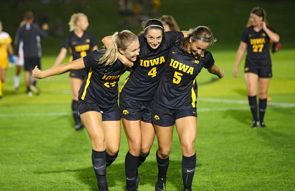Iowa defender Sara Wheaton (24), forward Kaleigh Haus (4), and defender Riley Whitaker (5) celebrate together after their match against Western Michigan at the Iowa Soccer Complex in Iowa City on Thursday, Aug 22, 2019. (Stephen Mally/hawkeyesports.com)
