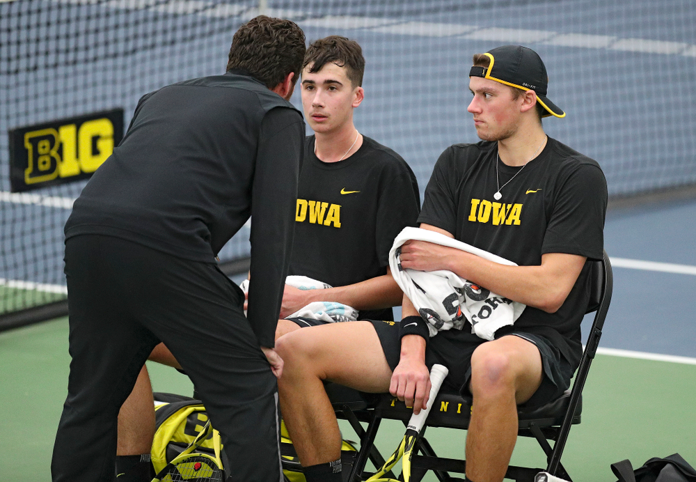 Iowa's Mellecker Family head men's tennis coach Ross Wilson (from left) talks with Matt Clegg and Joe Tyler during their doubles match against Marquette at the Hawkeye Tennis and Recreation Complex in Iowa City on Saturday, January 25, 2020. (Stephen Mally/hawkeyesports.com)