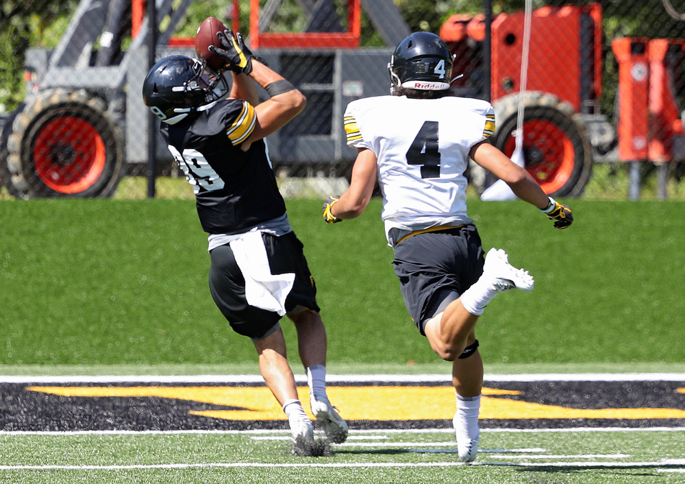 Iowa Hawkeyes wide receiver Nico Ragaini (89) pulls in a pass for a touchdown as defensive back Dane Belton (4) gives chase during Fall Camp Practice No. 7 at the Hansen Football Performance Center in Iowa City on Friday, Aug 9, 2019. (Stephen Mally/hawkeyesports.com)