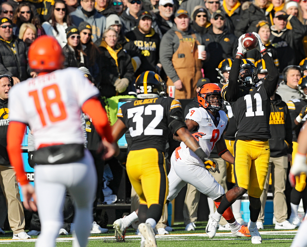 Iowa Hawkeyes defensive back Michael Ojemudia (11) intercepts a pass from Illinois Fighting Illini quarterback Brandon Peters (18) during the first quarter of their game at Kinnick Stadium in Iowa City on Saturday, Nov 23, 2019. (Stephen Mally/hawkeyesports.com)