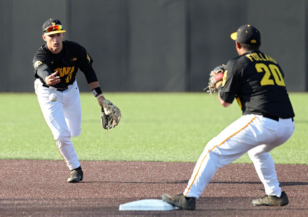 Iowa shortstop Dylan Nedved (from left) tosses the ball to infielder Izaya Fullard (20) as they turn a double play during the second inning of their college baseball game at Duane Banks Field in Iowa City on Tuesday, March 10, 2020. (Stephen Mally/hawkeyesports.com)