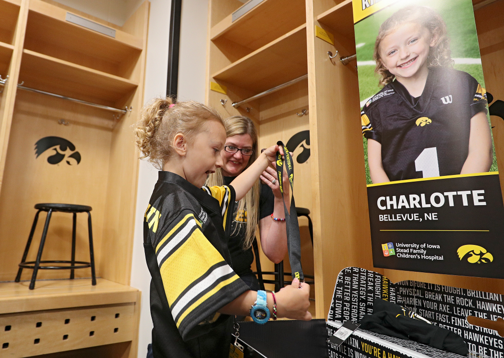 Kid Captain Charlotte Keller opens her box of gifts at her locker during Kids Day at Kinnick Stadium in Iowa City on Saturday, Aug 10, 2019. (Stephen Mally/hawkeyesports.com)