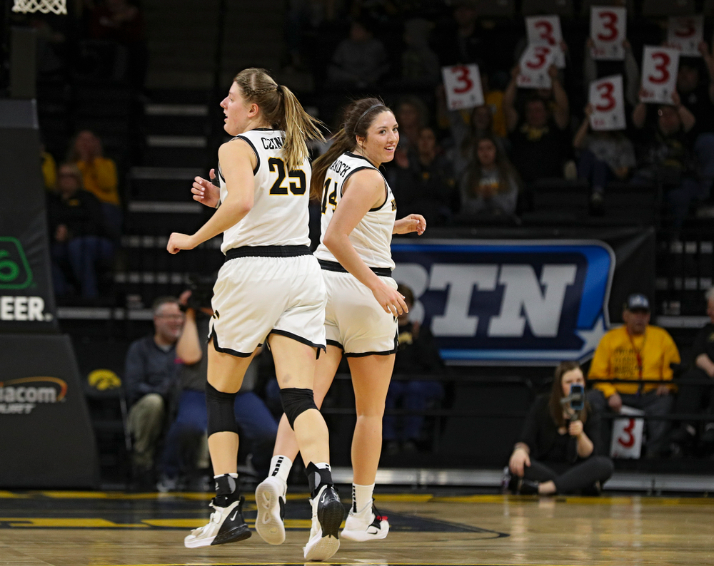 Iowa Hawkeyes guard Mckenna Warnock (14) smiles as she runs around forward Monika Czinano (25) after making a 3-pointer during the second quarter of their game at Carver-Hawkeye Arena in Iowa City on Sunday, January 26, 2020. (Stephen Mally/hawkeyesports.com)