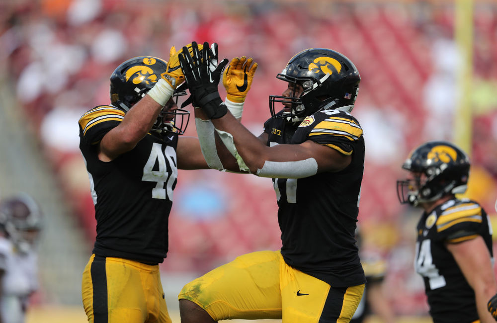 Iowa Hawkeyes defensive end Chauncey Golston (57) celebrates with linebacker Jack Hockaday (48) after intercepting a pass during the Outback Bowl Tuesday, January 1, 2019 at Raymond James Stadium in Tampa, FL. (Brian Ray/hawkeyesports.com)