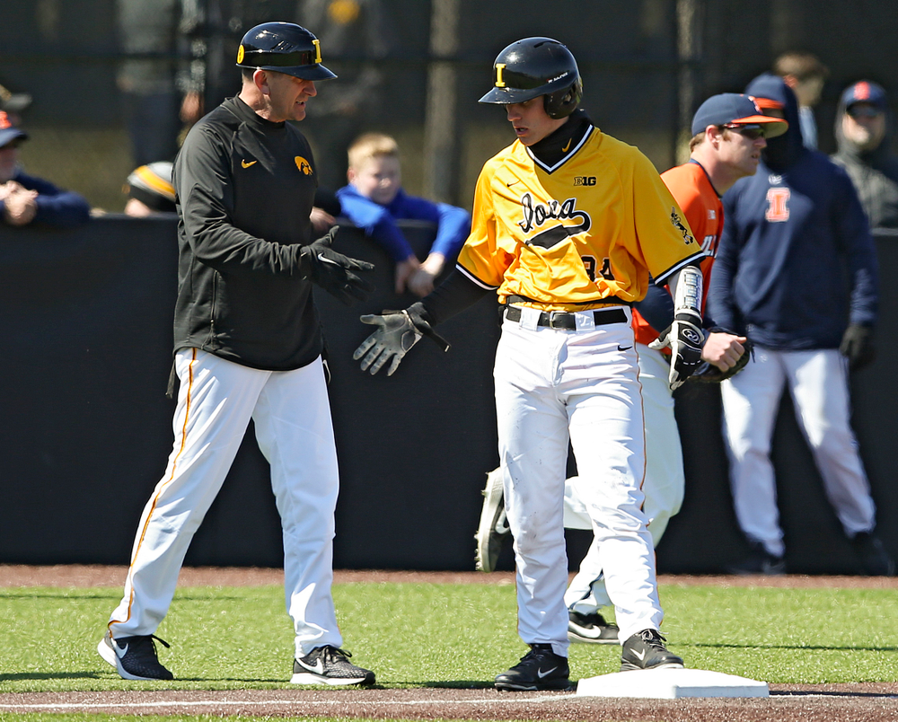 Iowa Hawkeyes head coach Rick Heller shakes hands with catcher Austin Martin (34) after he hit a 2-run triple during the third inning against Illinois at Duane Banks Field in Iowa City on Sunday, Mar. 31, 2019. (Stephen Mally/hawkeyesports.com)