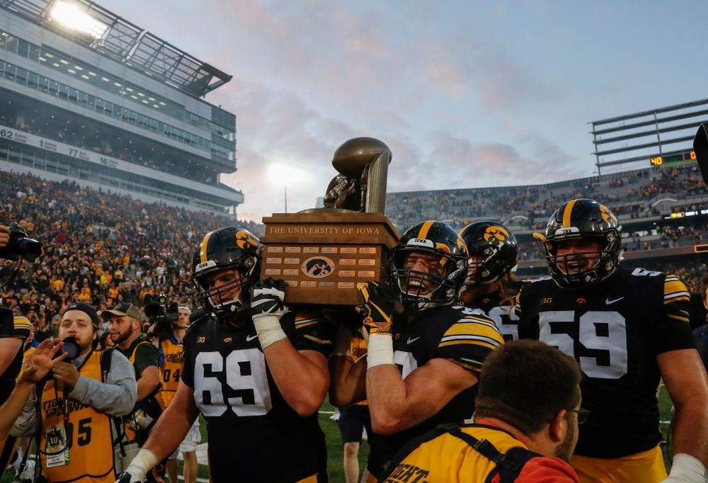 Iowa Hawkeyes offensive lineman Keegan Render (69) and defensive back Jake Gervase (30), offensive lineman Ross Reynolds (59) celebrate with the Cy-Hawk trophy following their game against the Iowa State Cyclones Saturday, September 8, 2018 at Kinnick Stadium. (Brian Ray/hawkeyesports.com)