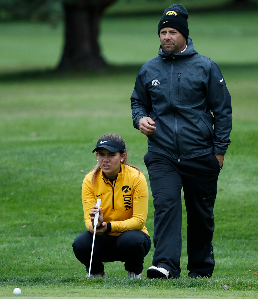 Iowa's Manuela Lizarazu gets advice from Iowa assistant coach Michael Roters as she lines up her putt during the Diane Thomason Invitational at Finkbine Golf Course on September 29, 2018. (Tork Mason/hawkeyesports.com)