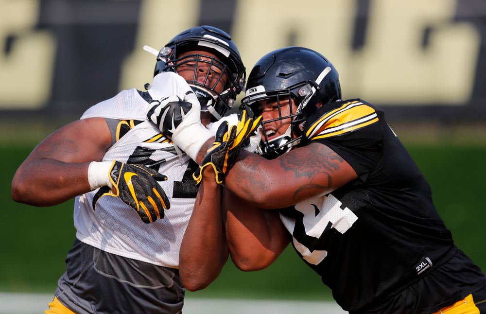 Iowa Hawkeyes defensive end Chauncey Golston (57) and offensive lineman Tristan Wirfs (74) during camp practice No. 16 Tuesday, August 21, 2018 at the Hansen Football Performance Center. (Brian Ray/hawkeyesports.com)