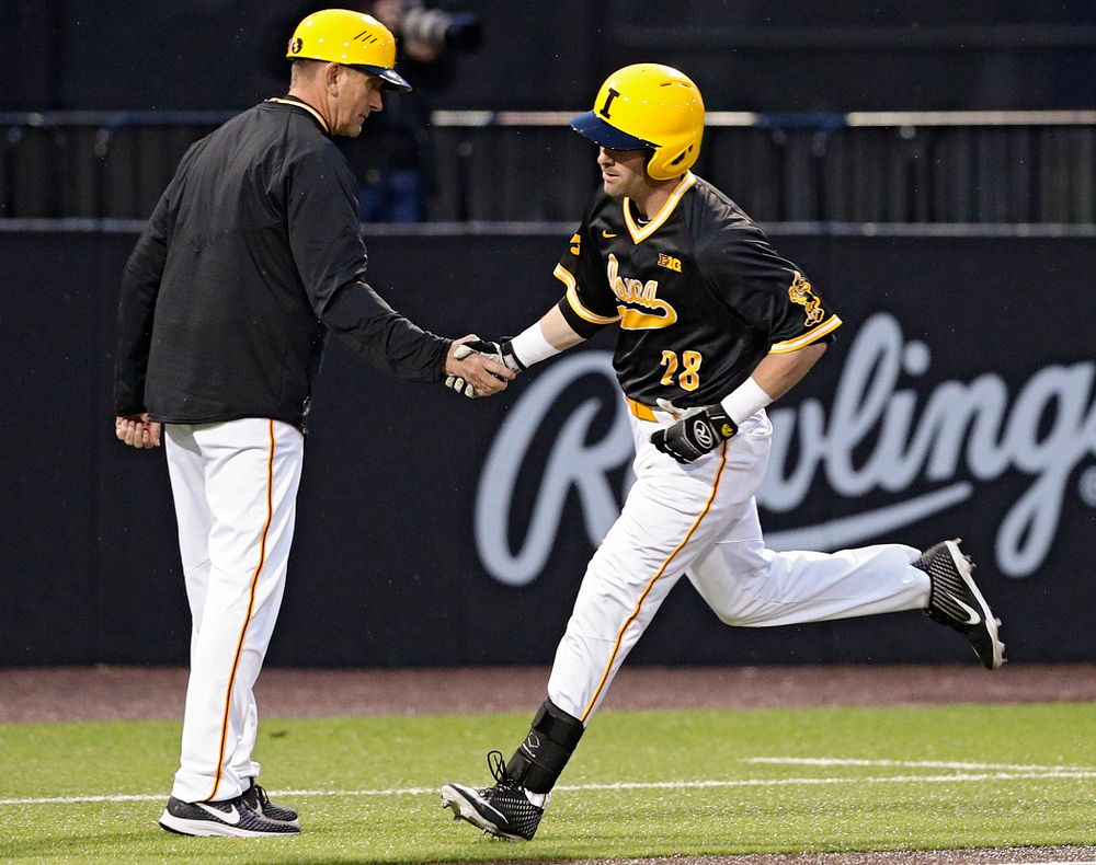 Iowa Hawkeyes head coach Rick Heller shakes hands with left fielder Chris Whelan (28) as he rounds third base after hitting a 3-run home run during the ninth inning of their game against Illinois State at Duane Banks Field in Iowa City on Wednesday, Apr. 3, 2019. (Stephen Mally/hawkeyesports.com)