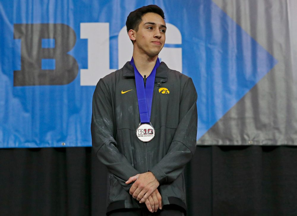 Iowa's Andrew Herrador receives a silver medal for his second place finish in the parallel bars during the second day of the Big Ten Men's Gymnastics Championships at Carver-Hawkeye Arena in Iowa City on Saturday, Apr. 6, 2019. (Stephen Mally/hawkeyesports.com)
