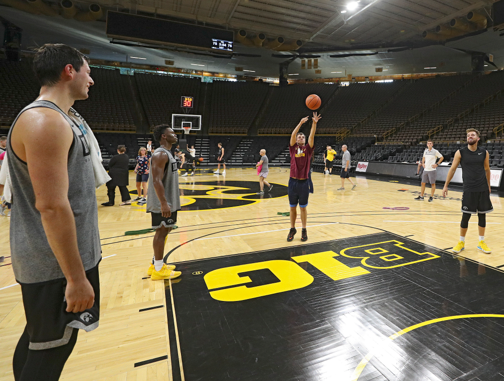 Iowa Hawkeyes forward Ryan Kriener (15), guard Joe Toussaint (1), and guard Jordan Bohannon (3) shoot free throws with visitors from the University of Iowa Hospitals and Clinics Adolescent and Young Adult (AYA) Cancer Program after practice at Carver-Hawkeye Arena in Iowa City on Monday, Sep 30, 2019. (Stephen Mally/hawkeyesports.com)